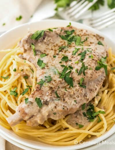Crock-Pot ranch pork chops on a bed of noodles garnished with parsley