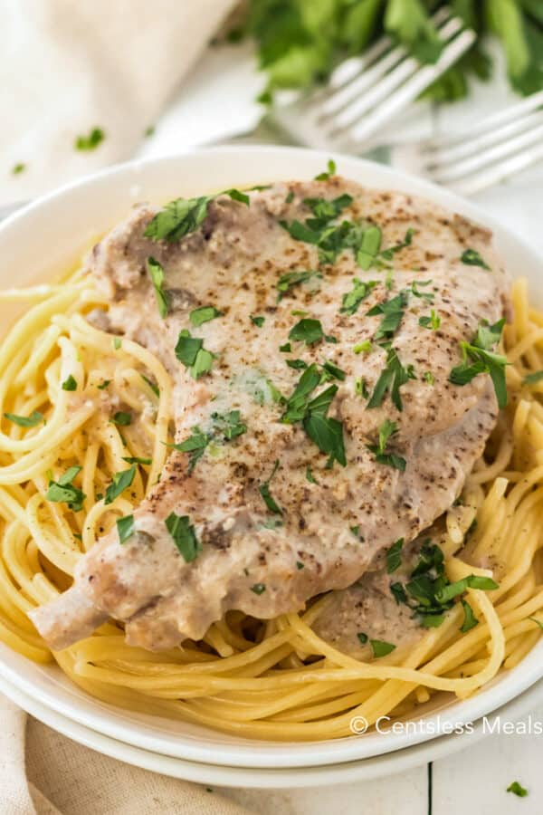 A cooked Crock Pot Ranch Pork Chop served over a plate of spaghetti. Garnished with fresh parsley.