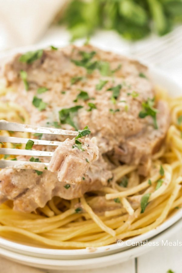 Close up of Crock Pot Ranch Pork Chops on a plate of spaghetti. A bite is being removed with a fork.