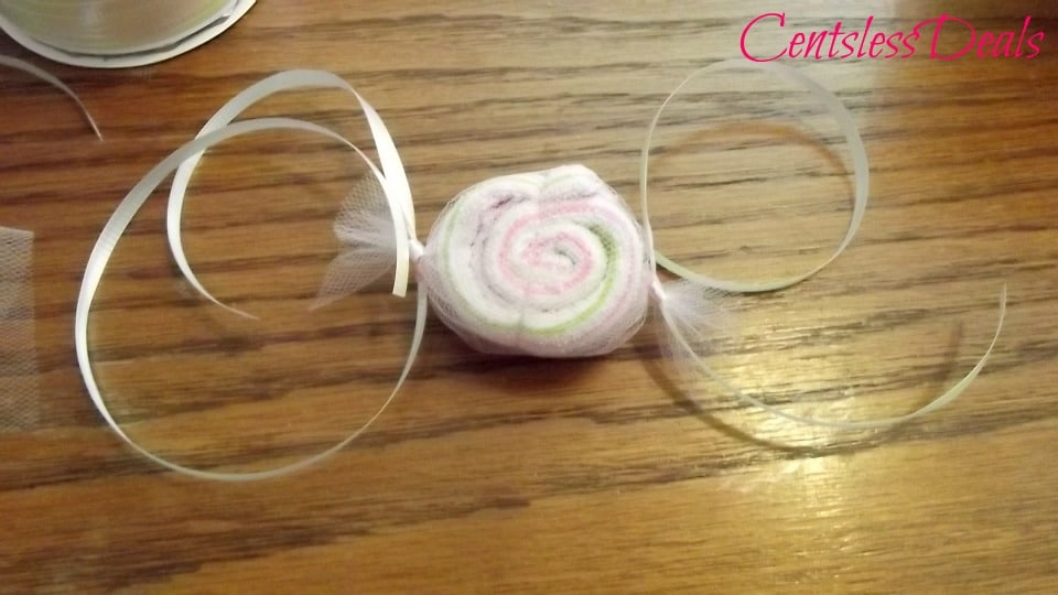 Washcloth candy on a table top with uncurled ribbon