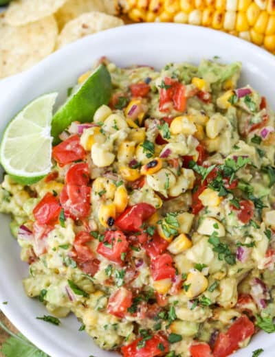 Grilled corn guacamole in a white bowl with lime wedges