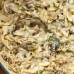 Creamy beef mushroom stroganoff in a pot with a spoon garnished with pepper and green onion