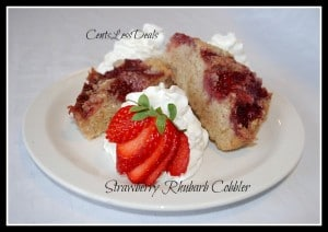 strawberry rhubarb cobbler on a plate with strawberry and whipping cream garnish