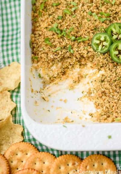Jalapeno popper dip in a white casserole dish with a scoop taken out