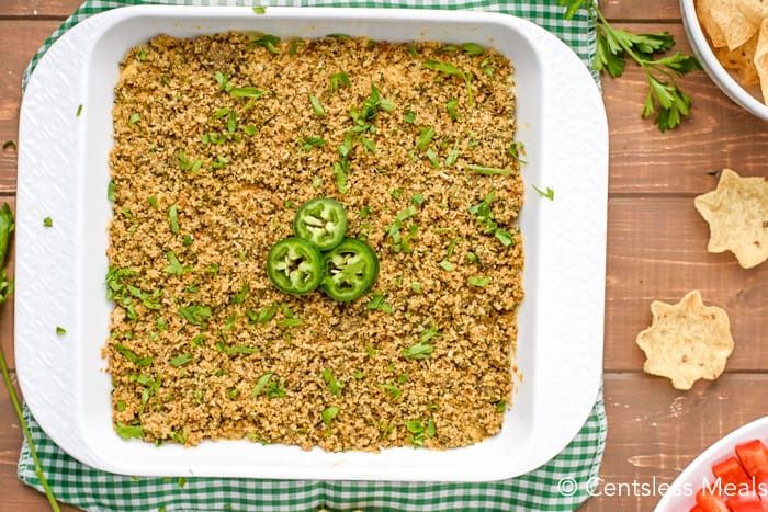Jalapeno popper dip in a white casserole dish with jalapenos and cilantro