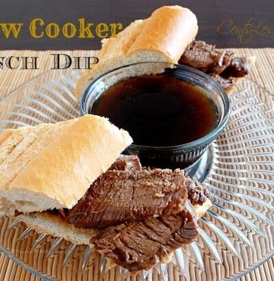 slow cooker french dip on a clear plate with a bowl of Au Jus