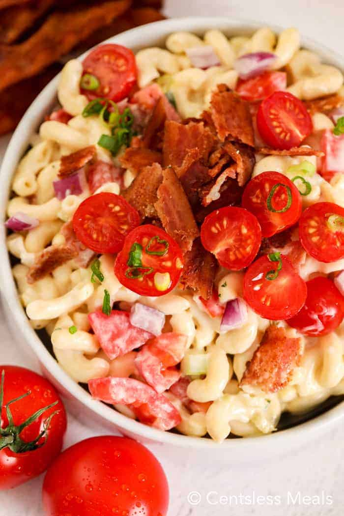 Bacon ranch macaroni salad in a white bowl topped with bacon and tomatoes