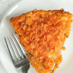 Slice of Doritos pie on a plate with a fork