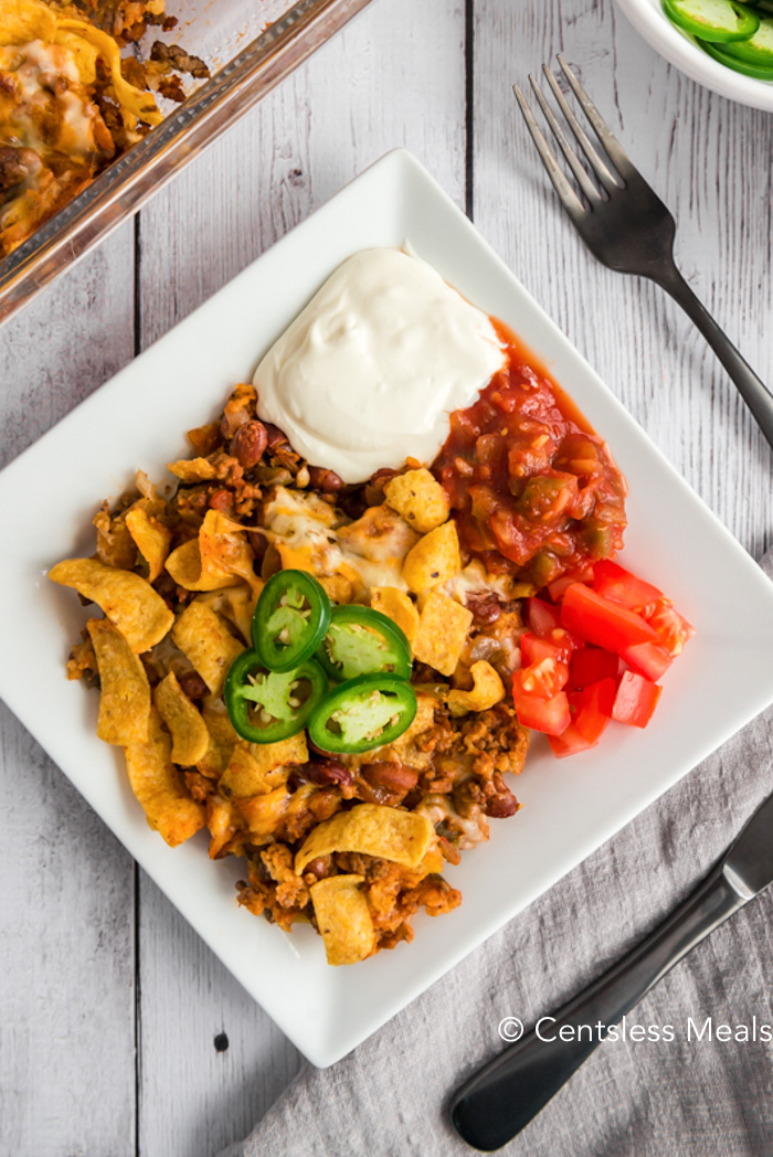 A top photo of Frito Pie garnished with jalapeños and a side of sour cream, salsa and tomatoes.