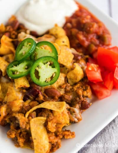Frito pie on a plate topped with jalapenos