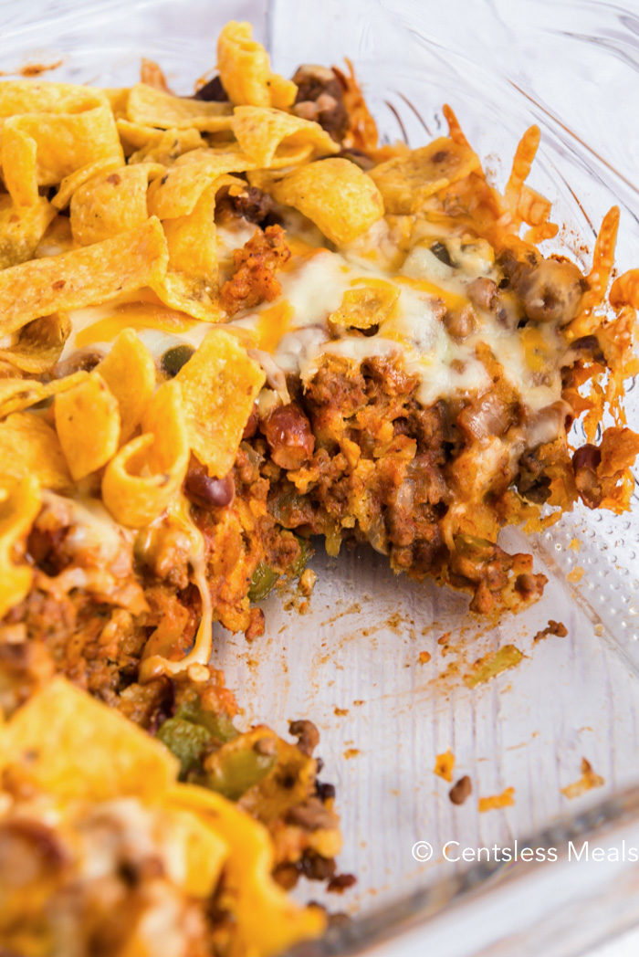A serving of Frito Pie is taken out of the clear casserole dish
