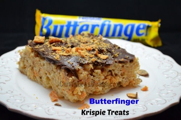 Butterfinger Rice Krispie Treats on a white plate with butter finger bar in the background