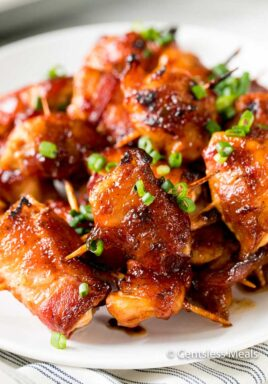 BBQ bacon wrapped chicken bites on a plate garnish with green onions