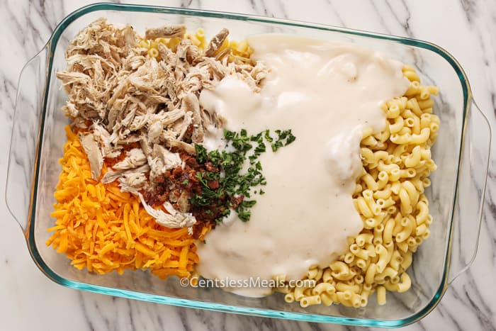 Ingredients to make Chicken Mac and Cheese with bacon, assembled in a clear casserole dish.