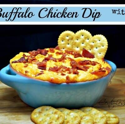 Buffalo chicken dip with bacon in a blue bowl with crackers and writing