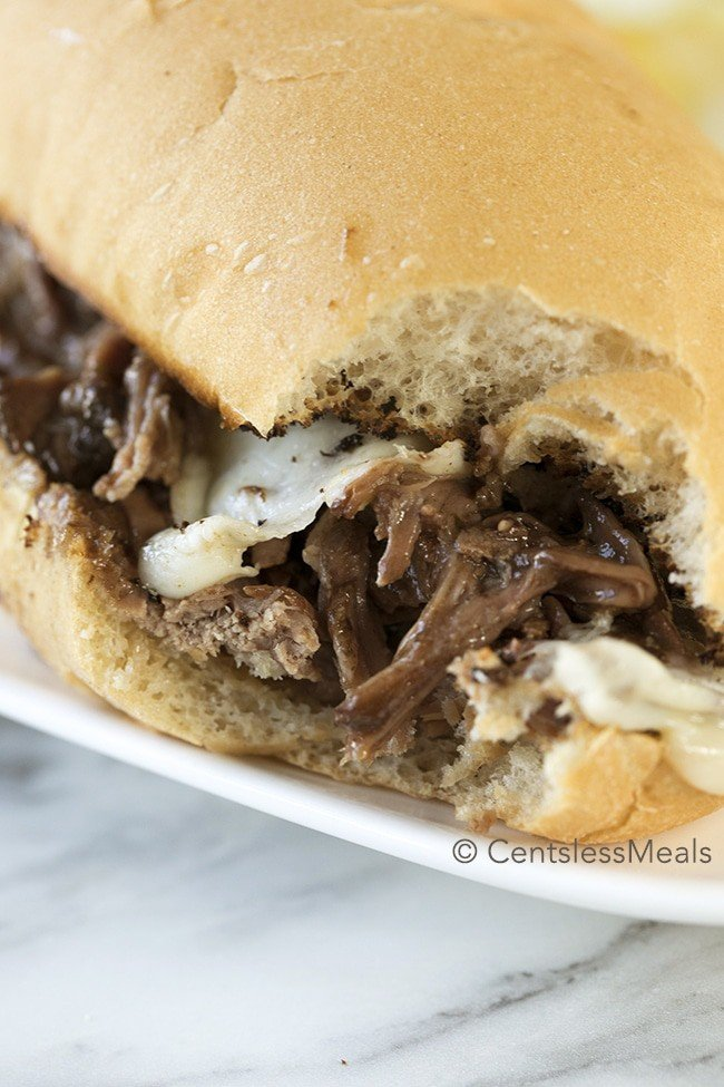 A tender crock pot Italian beef sandwich topped with cheese