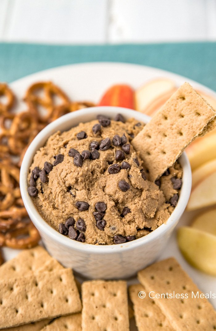 Edible cookie dough in a white bowl with a cracker being dipped in