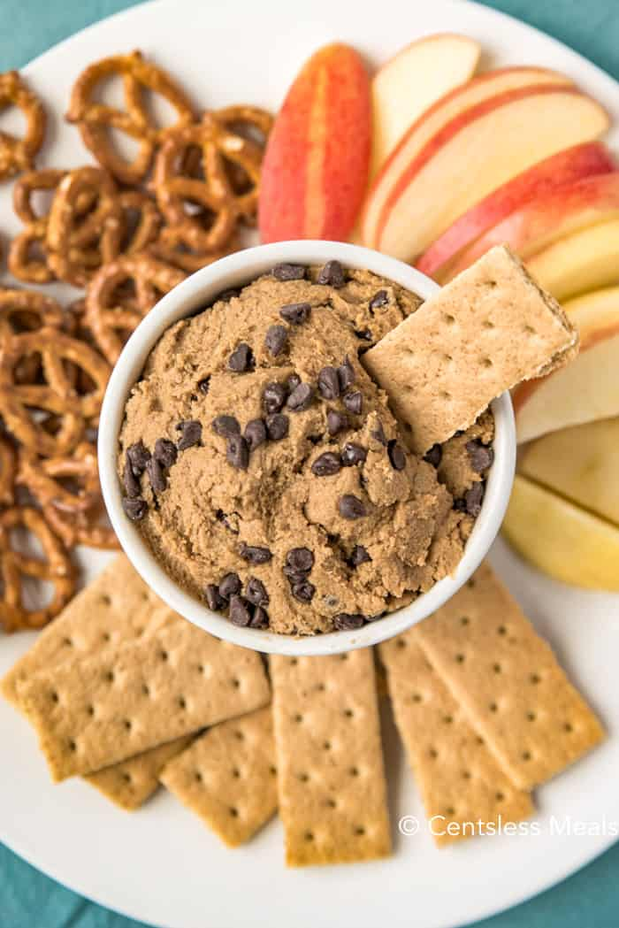 Edible cookie dough in a white bowl with crackers pretzels and apples