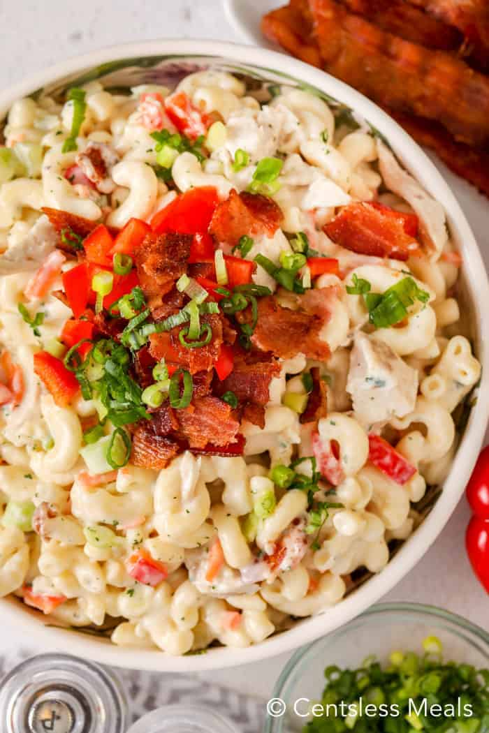 Top view of macaroni salad with bacon and chicken in a ranch dressing, garnished with bacon and chives.