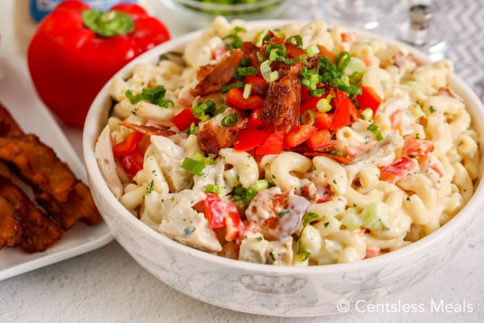 Ranch Macaroni Salad in a bowl, with slices of bacon beside it.