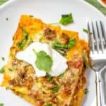 Taco bake on a white plate with a fork and cilantro