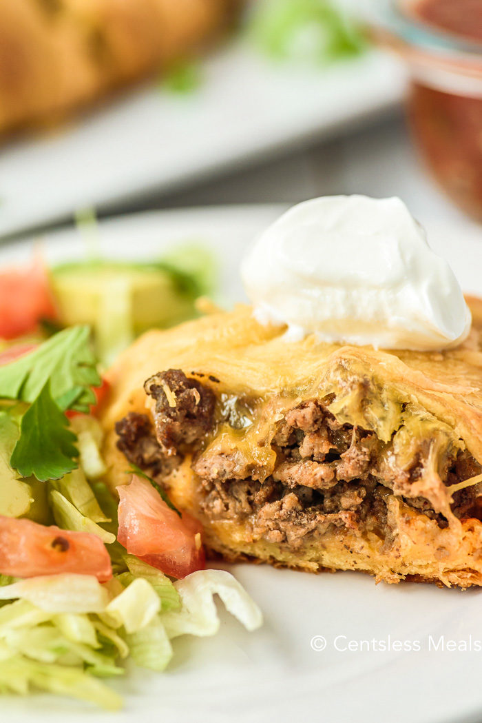 A close up photo of baked taco ring with a dollop of sour cream on top and a fresh salad on the side of the white plate