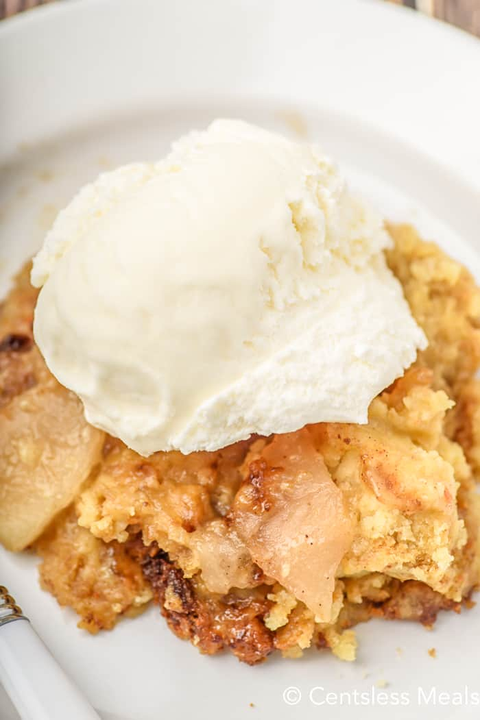 Crock pot apple cobbler on a white dish topped with ice cream
