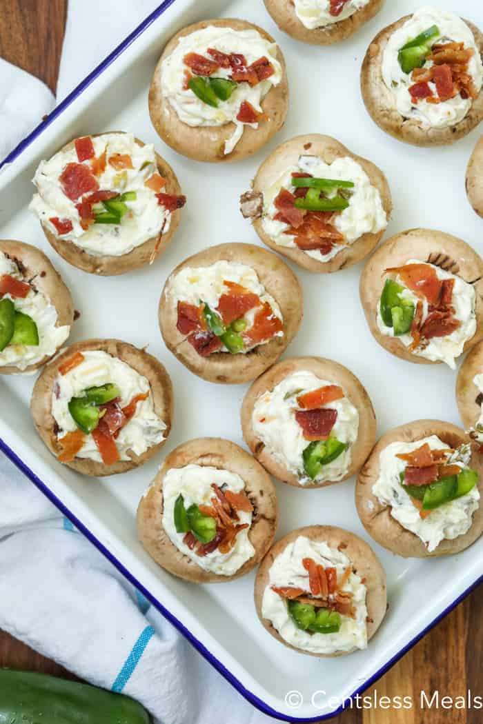 Stuffed mushrooms, with bacon and jalapenos, on a white baking dish with a blue rim.
