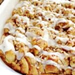 Cinnamon roll french toast casserole in a white dish drizzled with icing