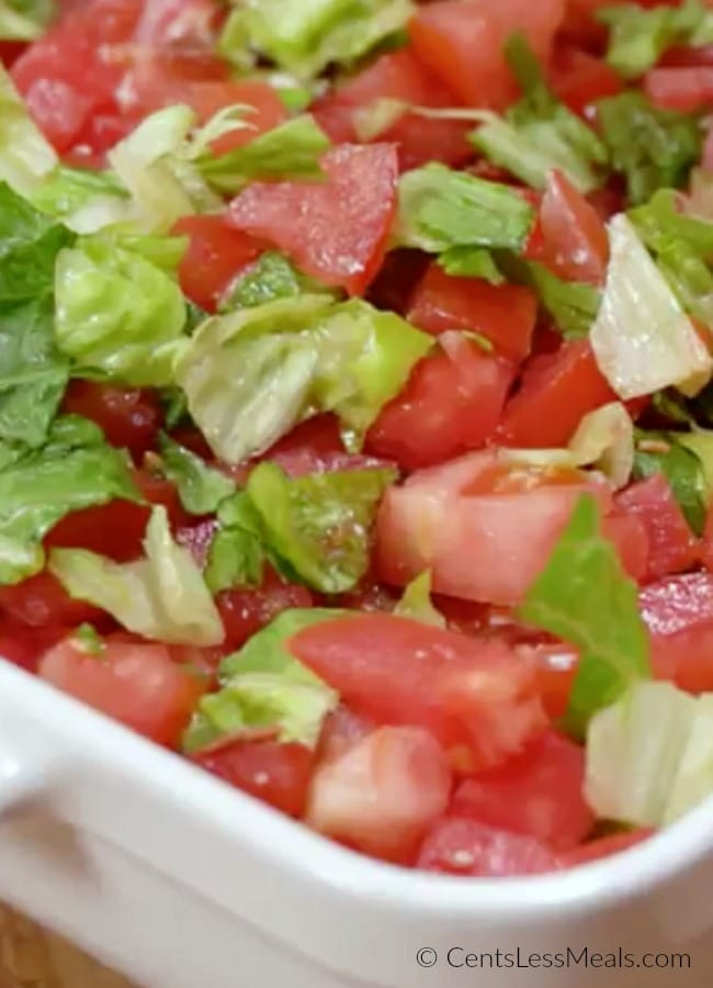 Creamy BLT dip in a dish topped with lettuce and tomato