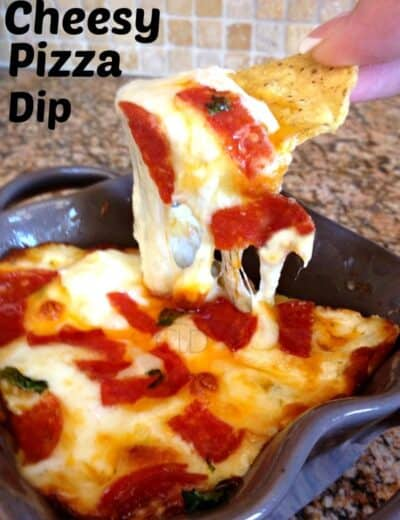 Cheesy pizza dip in a dish being dipped with a tortilla chip with a title