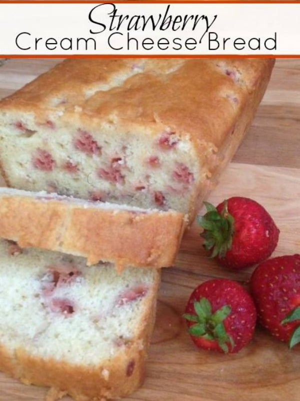 Strawberry cream cheese bread on a wooden board with strawberries on the side and a title