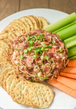 Bacon Ranch Cheeseball on a plate with crackers, celery and carrots
