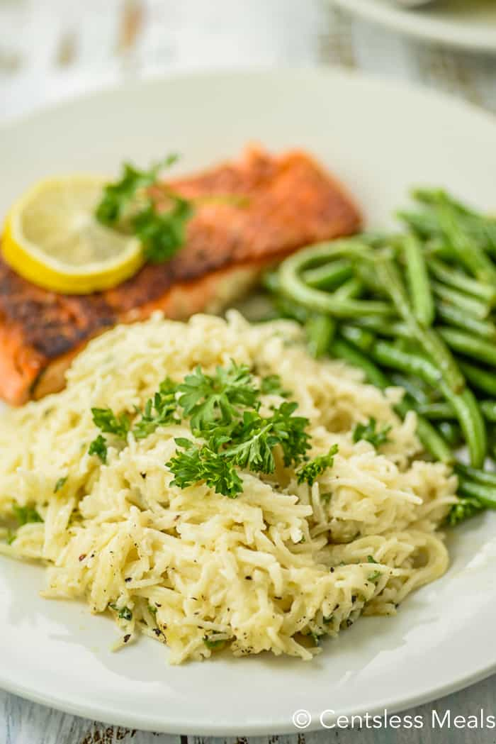 Garlic pasta on a plate with fish and green beans