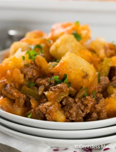 Sloppy joe tater tot casserole on a white plate garnished with parsley