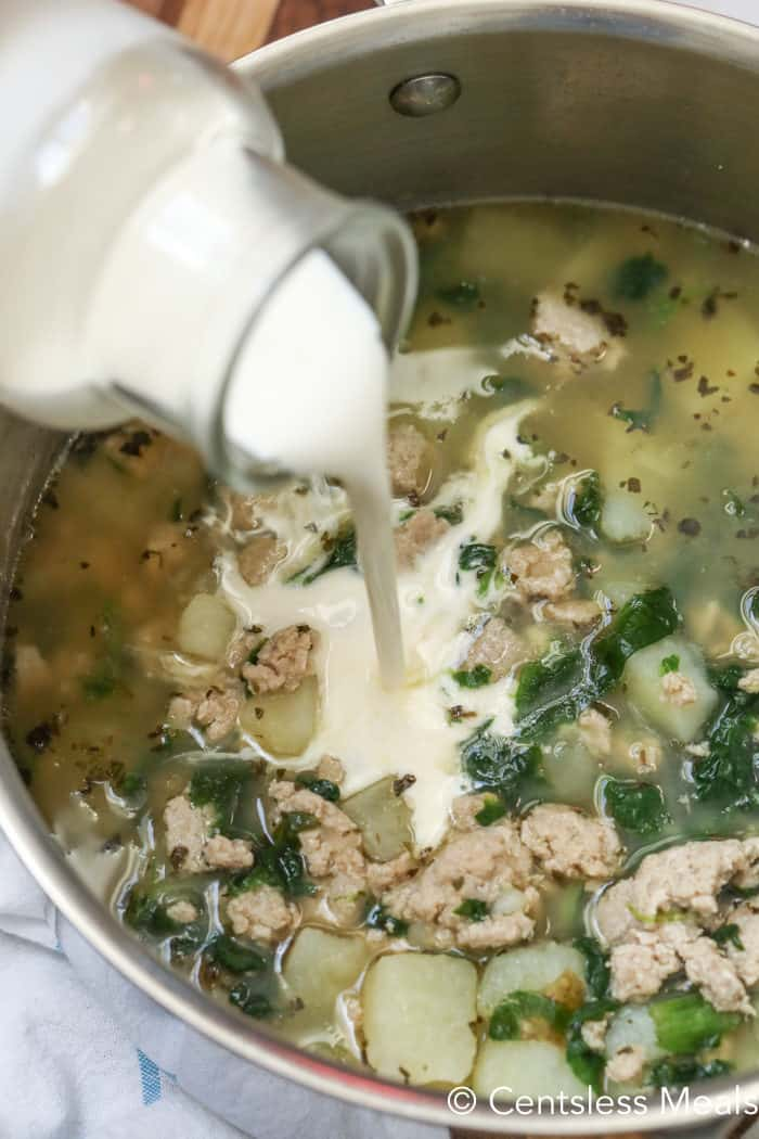 Zuppa Toscana soup in a pot with milk being poured in