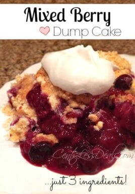 Mixed berry dump cake on a plate with whipped cream and writing