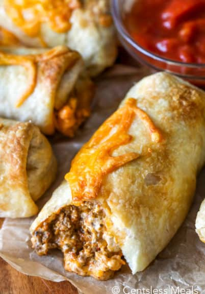 Taco pockets on parchment paper with salsa in the background
