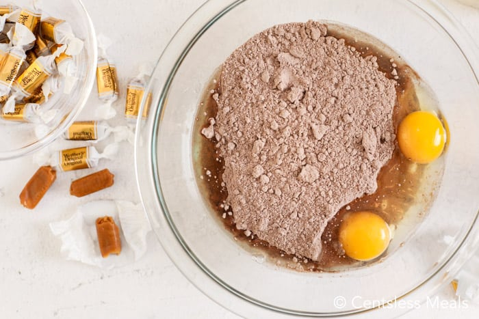 ingredients for cake mix cookies in a clear bowl, with caramels on the side