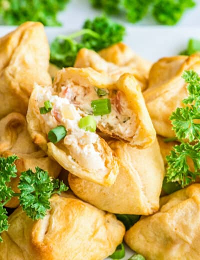 Crab and cheese filled crescent rolls on a plate with parsley and green onions