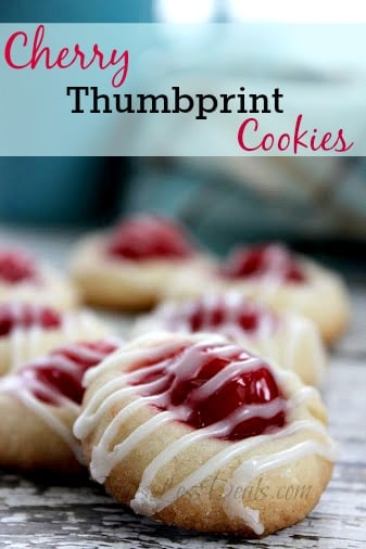 Cherry thumbprint cookies on a wooden board with a title