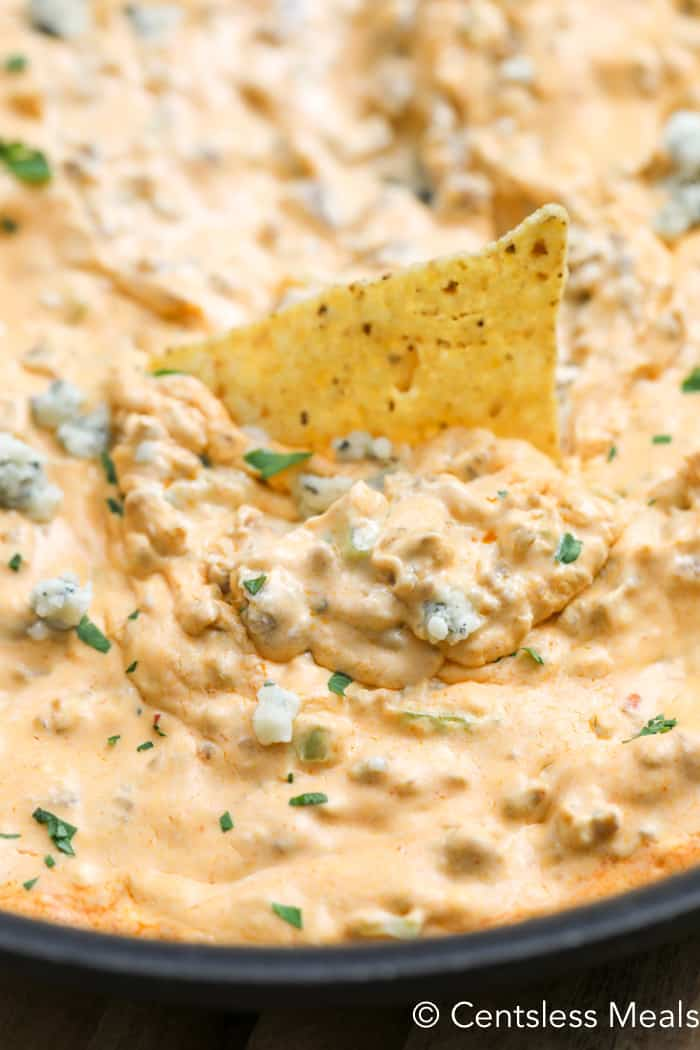 Buffalo Sausage Dip in a bowl with a tortilla chip in the middle.