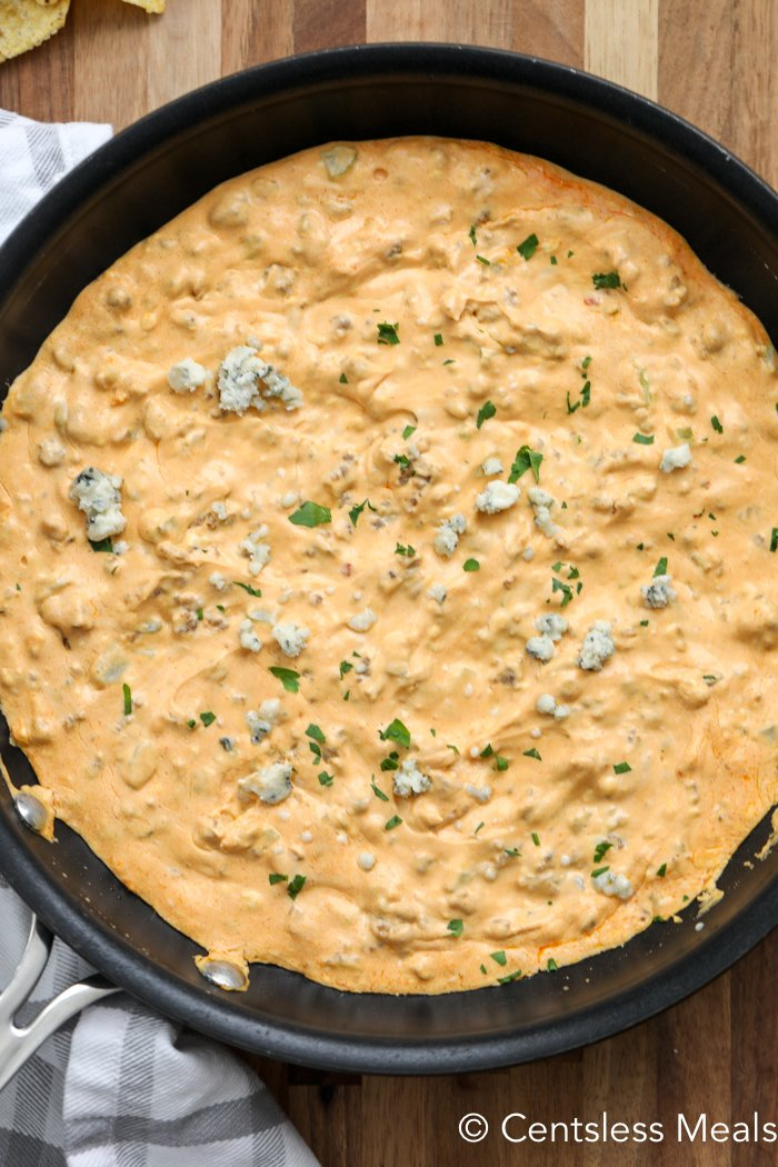 Overhead shot of buffalo sausage dip in a frying pan sprinkled with parsley and blue cheese.