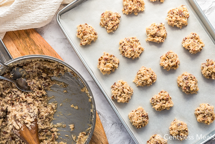 Coconut pecan cookies being scooped onto a cookie sheet with parchment paper.