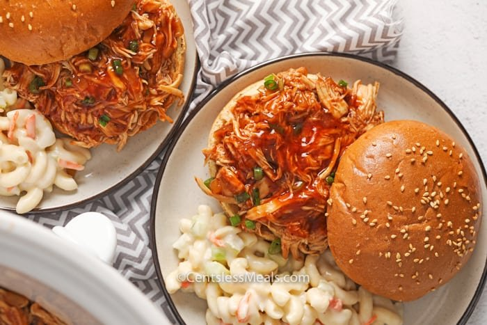 Crock-Pot BBQ beer chicken sandwiches on two plates with macaroni salad on the side