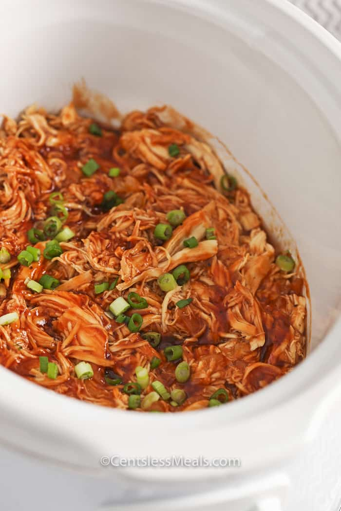 Crock-Pot BBQ beer chicken in a Crock-Pot garnished with green onion