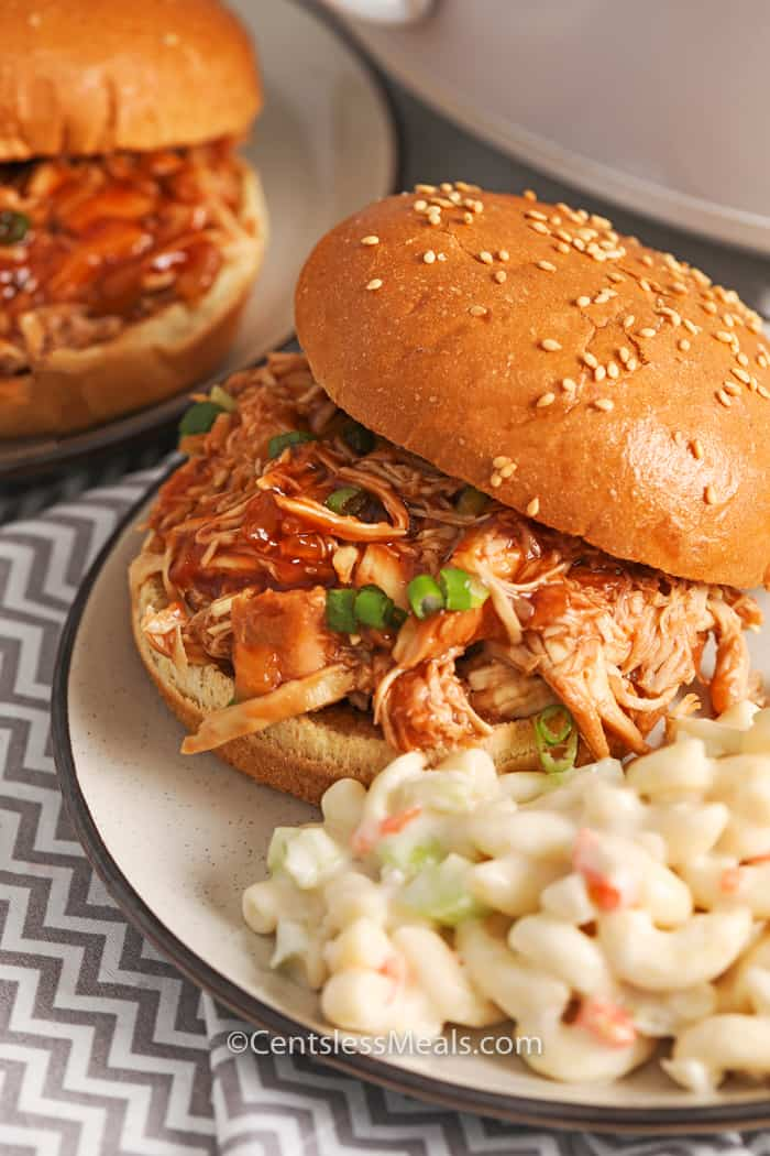 Crock-Pot BBQ beer chicken sandwiches on plates garnished with green onion