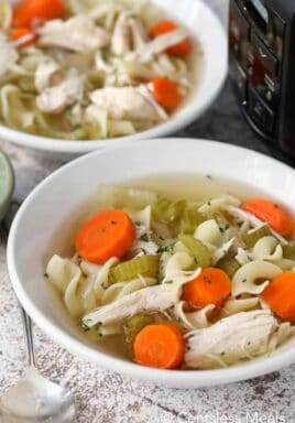 Chicken noodle soup into white bowls with a Crockpot on the side