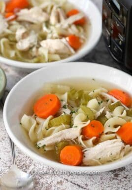 Crock-Pot chicken noodle soup in white bowls with a spoon on the side