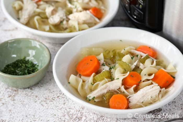 CrockPot Chicken Noodle Soup in a white bowl, with fresh chopped parsley on the side.